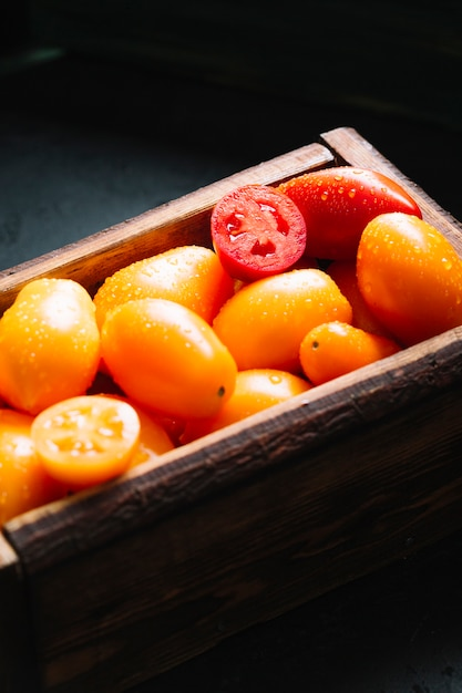 Vista alta da cesta cheia de tomates Foto gratuita