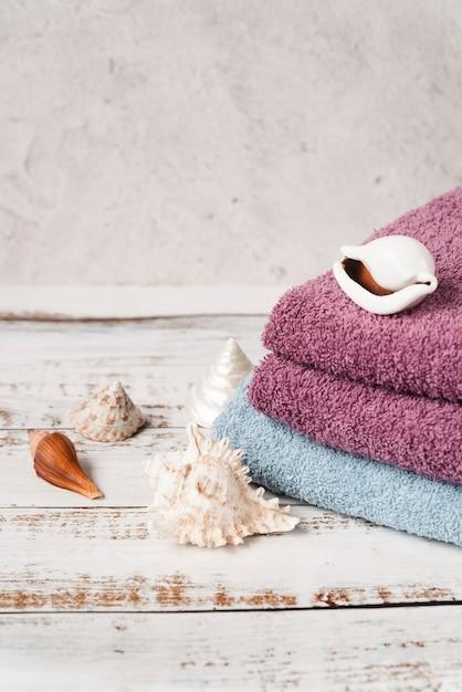 Vista alta empilhados toalhas na mesa de madeira Foto gratuita
