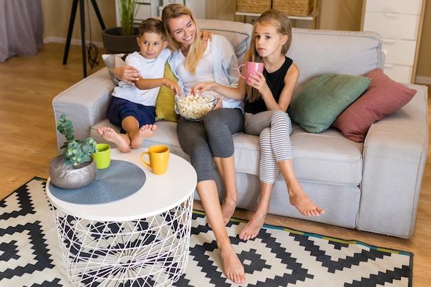 Vista alta mulher e filhos comendo pipoca Foto gratuita
