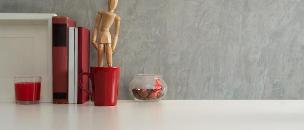 Vista aproximada da mesa de trabalho com livros, copo vermelho, moldura simulada e espaço de cópia no escritório doméstico Foto Premium