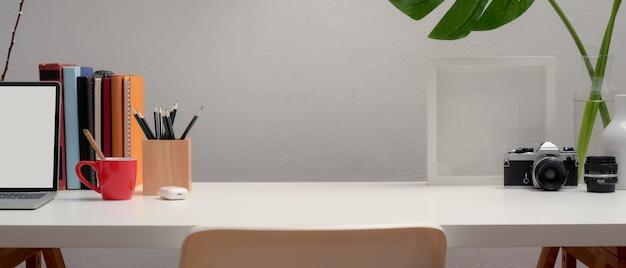 Vista aproximada do espaço de trabalho com simulação de laptop, artigos de papelaria, decorações, livros e espaço de cópia na mesa branca com cadeira Foto Premium