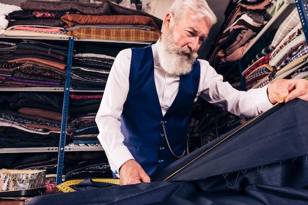 Vista baixa ângulo, de, macho sênior, alfaiate, fazendo medida, de, azul, tecido, com, medindo fita Foto gratuita