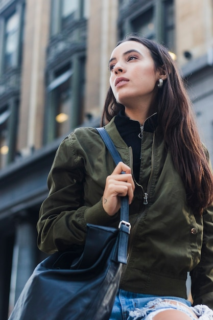 Vista baixa ângulo, de, mulher jovem, segurando, azul, bolsa, andar, rua Foto gratuita