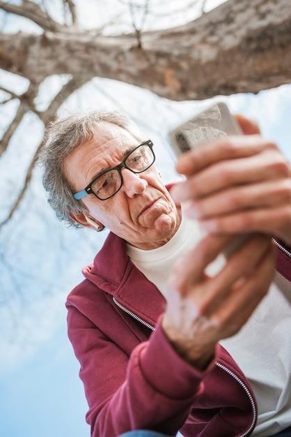 Vista baixa ângulo, de, sério, homem sênior, usando, esperto, telefone Foto gratuita