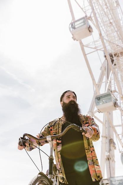 Vista baixa ângulo, de, um, homem jovem, montando, ciclo, perto, roda ferris Foto gratuita