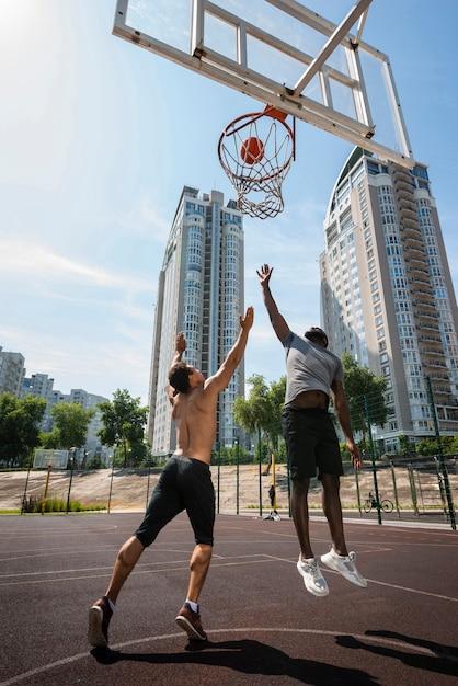 Vista baixa ângulo, de, um, homens jogando basquete Foto gratuita