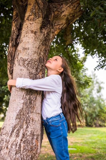 Vista baixa ângulo, de, um, menina, com, cabelos longos, abraçando, árvore Foto gratuita