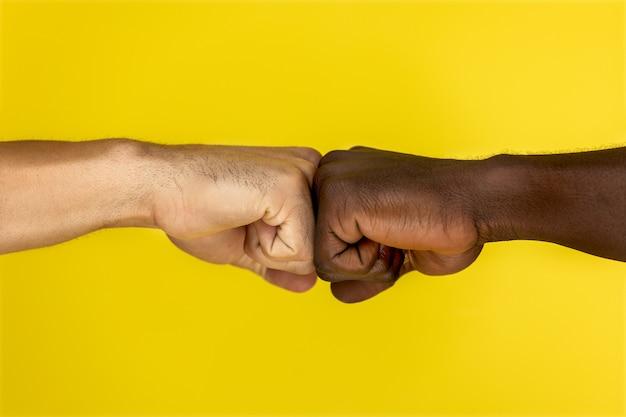 Vista central da mão européia e afro-americana em punhos cerrados Foto gratuita