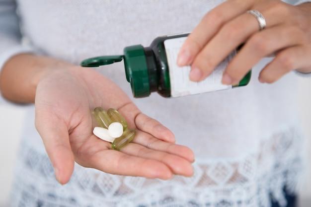 Vista colhida da mulher derramando comprimidos da garrafa Foto gratuita