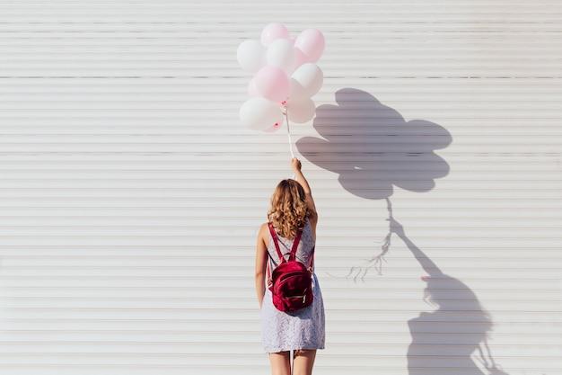 Vista, costas, jovem, mulher, mochila, segurando, ar, balões Foto gratuita