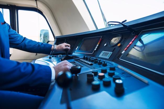 Vista da cabine do trem do metrô de alta velocidade e um maquinista irreconhecível empurrando a alavanca e acelerando o trem. Foto Premium