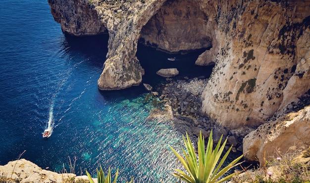 Vista da gruta azul e pequenos barcos com turistas Foto Premium