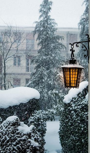 Vista da nevasca de inverno de dentro da casa com uma velha lâmpada acesa na lateral da casa Foto Premium