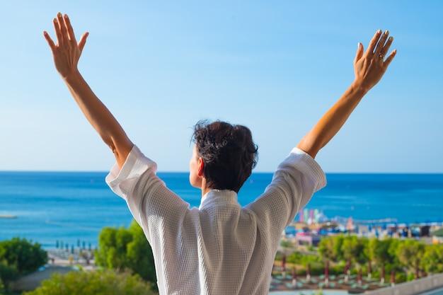 Vista da parte de trás de uma mulher com as mãos abertas na varanda na manhã de verão. Foto Premium