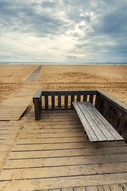 Vista da passagem de madeira em uma linha costeira vazia longa da praia. Foto Premium