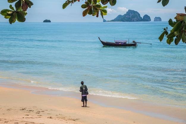 Vista da praia exótica em krabi tailândia. um homem olha para o barco longtaile da areia Foto Premium