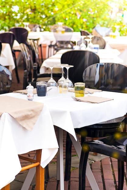 Vista da rua de um terraço de café com mesas e cadeiras. Foto Premium