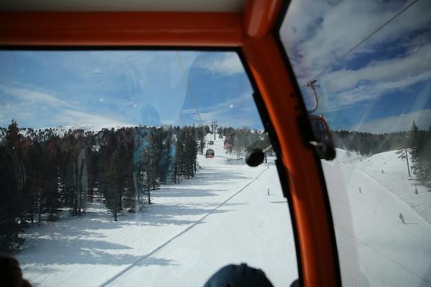 Vista das cabines de gôndola do teleférico elevador em montanhas nevadas de inverno fundo belas paisagens Foto Premium