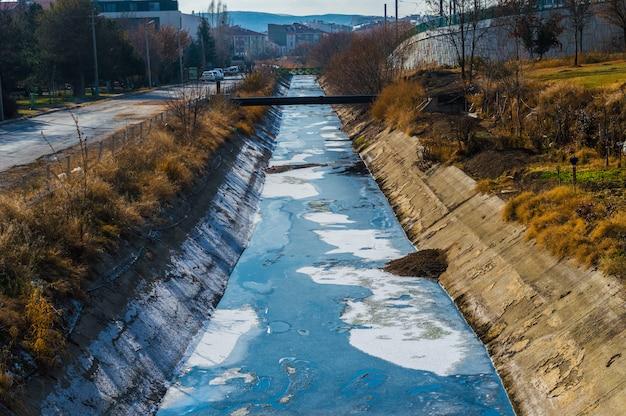 Vista de águas residuais, poluição e lixo em um canal Foto Premium