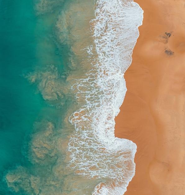 Vista de alto ângulo da praia e do mar sob a luz do sol - ótima para fundos e papéis de parede Foto gratuita