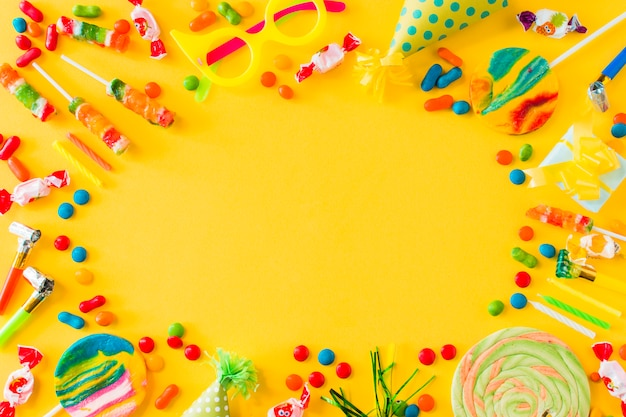 Vista de alto ângulo de doces; pirulitos; velas; festa e ventilador na superfície amarela Foto gratuita