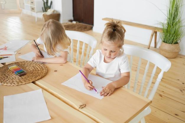 Vista de alto ângulo de dois irmãos, menina e irmão mais velho, sentados juntos à mesa de jantar de madeira, desenhando imagens em folhas de papel brancas, usando lápis coloridos. conceito de infância e criatividade Foto gratuita