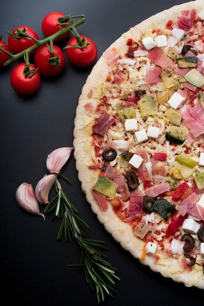 Vista de alto ângulo de enfeite saborosa pizza italiana sobre a bancada da cozinha Foto gratuita