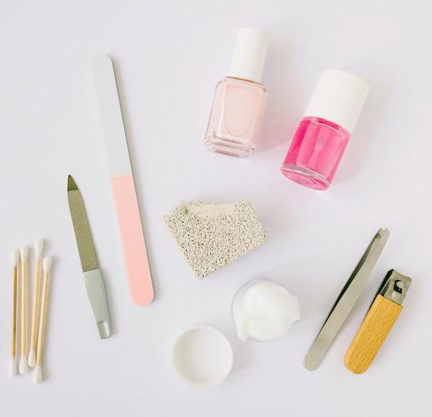 Vista de alto ângulo de ferramentas de manicure e produtos em pano de fundo branco Foto gratuita
