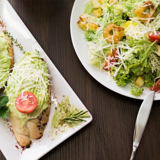 Vista de alto ângulo de pão com molho pesto; queijo ralado e tomate cereja no prato perto de salada sobre a mesa Foto gratuita
