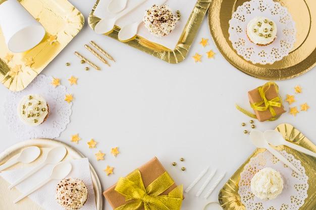 Vista de alto ângulo de presentes de aniversário; bolinho e velas no fundo branco Foto gratuita