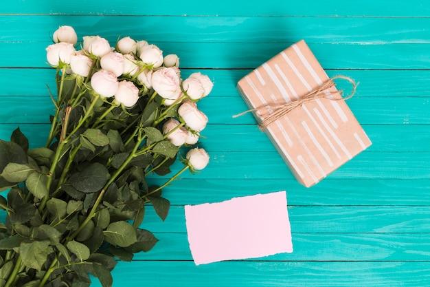 Vista de alto ângulo de rosas brancas; caixa de presente e papel em branco sobre o pano de fundo verde Foto gratuita