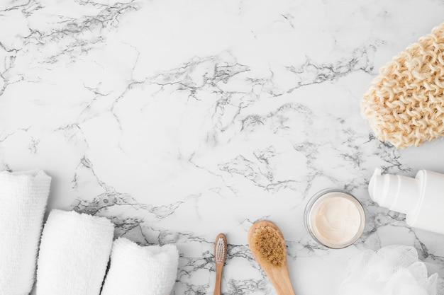 Vista de alto ângulo de toalhas; escova; creme hidratante; esponja; frasco cosmético e luva de esfrega na superfície de mármore Foto gratuita
