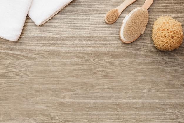 Vista de alto ângulo de toalhas; esponja e escova em fundo de madeira Foto gratuita