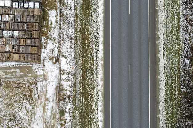 Vista de alto ângulo de uma estrada cercada por um prado coberto de neve com objetos metálicos Foto gratuita