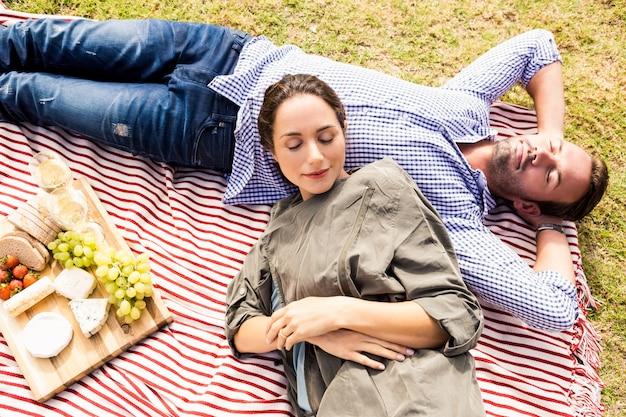 Vista de alto ângulo do casal dormindo na manta de piquenique Foto Premium