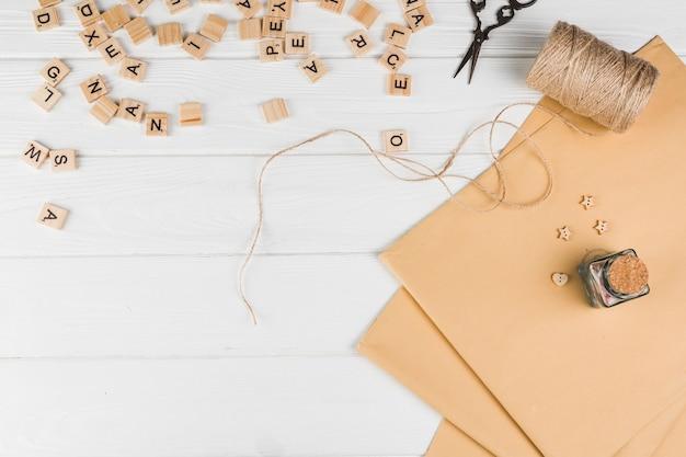 Vista de alto ângulo do cubo de texto de madeira; tesoura carretel de corda com papel marrom na mesa branca Foto gratuita