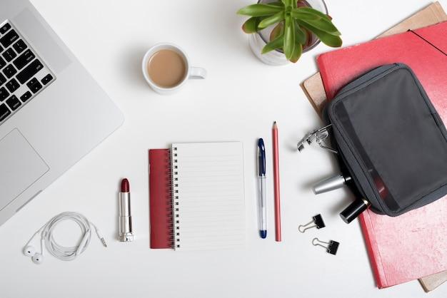 Vista de alto ângulo do laptop; bolsa de maquiagem; fone de ouvido e xícara de café e arquivos sobre a mesa branca Foto gratuita