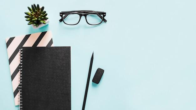 Vista de alto ângulo do notebook; lápis; borracha e óculos em fundo azul Foto gratuita