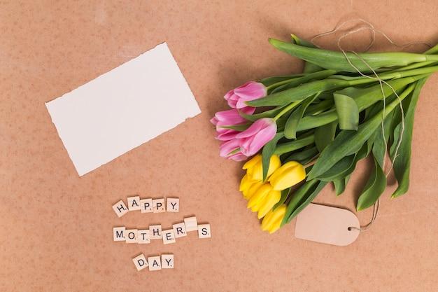 Vista de alto ângulo do texto feliz dia das mães; papel em branco e amarelo; flores tulipa rosa acima do pano de fundo marrom Foto gratuita
