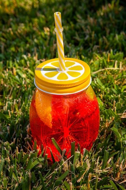 Vista de alto ângulo, um copo de suco de fruta na grama. vertical Foto gratuita