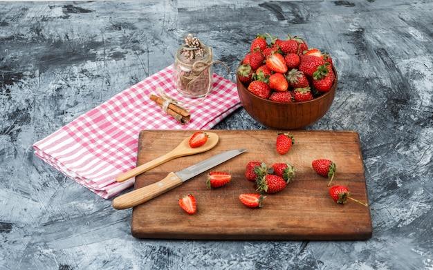 Vista de alto ângulo uma jarra de vidro e canela na toalha de mesa riscada vermelha com utensílios de cozinha e uma tigela de morangos na superfície de mármore azul escuro. horizontal Foto gratuita