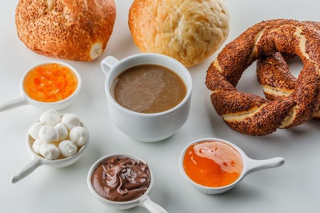 Vista de alto ângulo, uma xícara de café com geléias, açúcar, chocolate em xícaras, pão turco, pão na superfície branca Foto gratuita