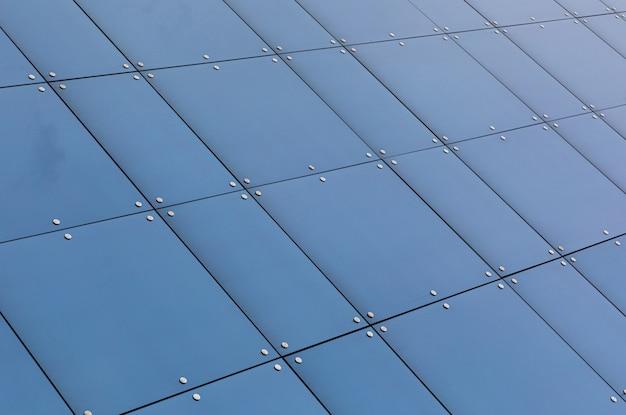 Vista de ângulo baixo da reflexão de vidro azul na construção de fachada Foto Premium