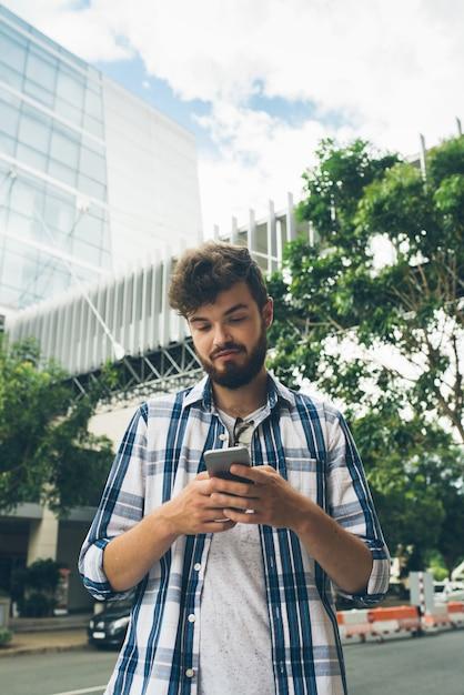 Vista de ângulo baixo de mensagens de texto de cara hipster em smartphone no meio da rua Foto gratuita