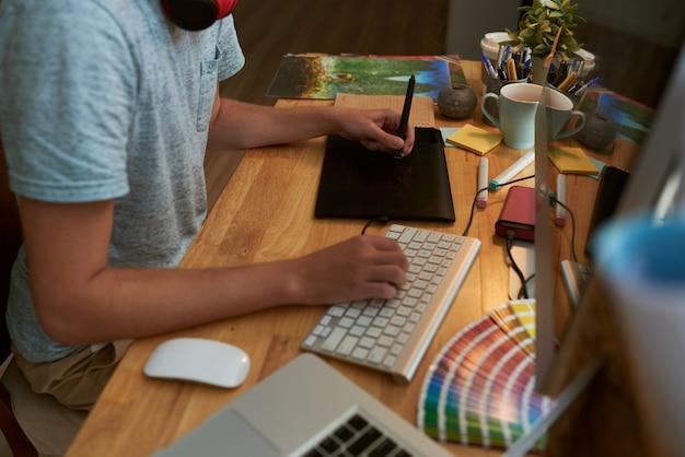 Vista de ângulo superior do web designer masculino no trabalho Foto gratuita