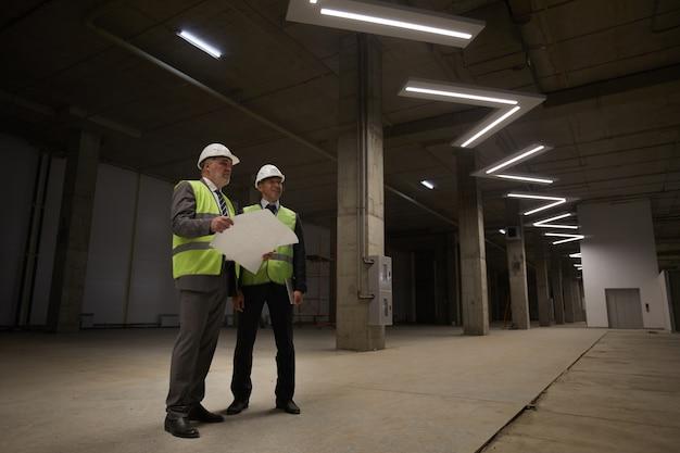 Vista de baixo ângulo para dois empresários usando capacetes e segurando planos enquanto estavam no canteiro de obras, Foto Premium