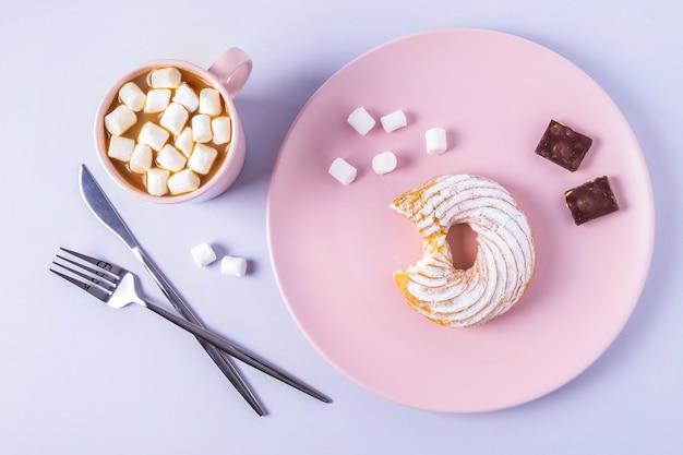 Vista de cima ainda a vida de um bolo mordido em um prato rosa, talheres e uma xícara de chocolate quente com marshmallows. foco seletivo, orientação horizontal. Foto Premium