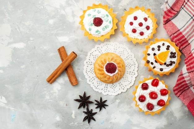 Vista de cima bolinhos com creme de canela e frutas diferentes isoladas na superfície leve açúcar doce Foto gratuita