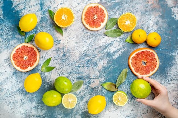 Vista de cima, círculo, linha, frutas cítricas, limões, toranjas, tangerinas, limão, mulher, mão, azul, mesa Foto gratuita