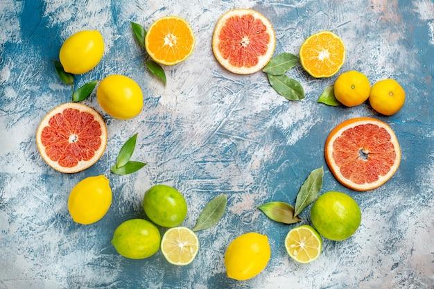 Vista de cima, círculo, linha, frutas cítricas, limões, toranjas, tangerinas, mesa, azul, branco Foto gratuita